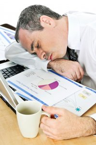 Businessman asleep at his desk on white background