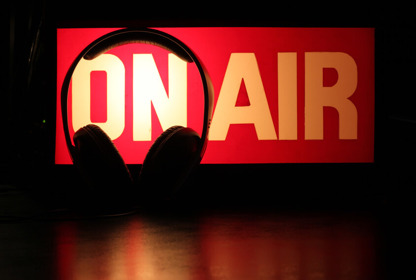 Headphones silhouette against On-Air sign symbolising a podcast broadcast.